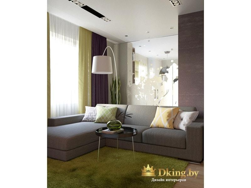 серый угловой диван с простыми формами. на полу ковер, по фактуре и цвету напоминающиу траву. В углу большой белый торшер. Потолок белый, одноуровневый