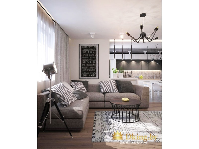 большой угловой серый диван в гостиной, лакончиная форма мебели, необычный круглый журнальный стол в виде тумбы. На стене грифельная доска, на полу серый ковер с орнаментов без ворса