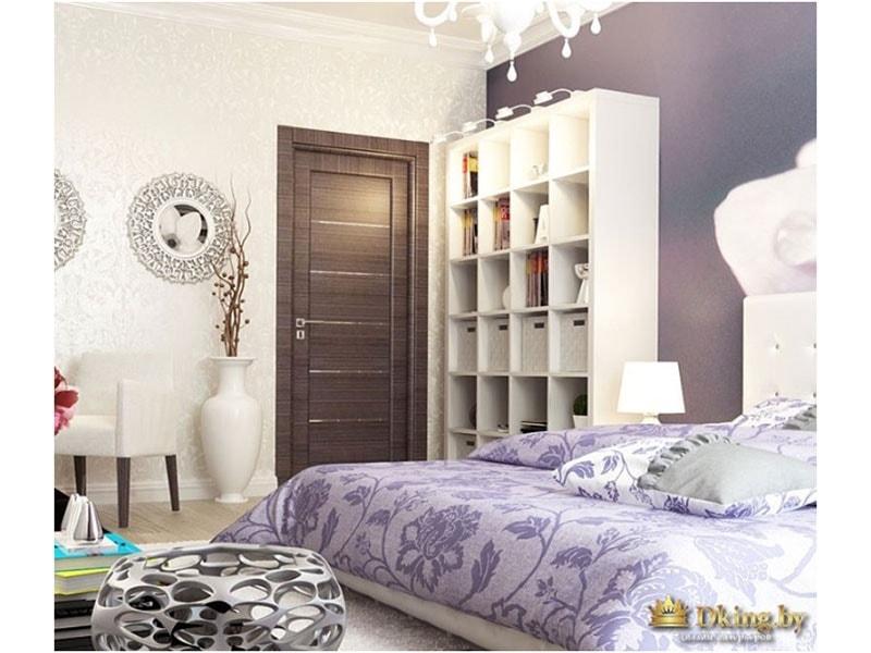 В интерьере выдержаны классические ноты: ваза, фиолетовое цветочное покрывало, книжный шкаф и классическая люстра