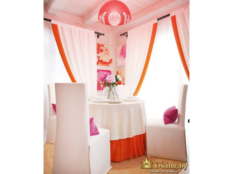 столовая группа: круглый стол с двойной скатертью (верхний слой белый, нижний ярко-оранжевый. шторы на окнах белые с подхватами и ярким оранжевым кантом, стулья в белых чехлах до пола. Над столом оранжевый светильник, на потолке - балки.