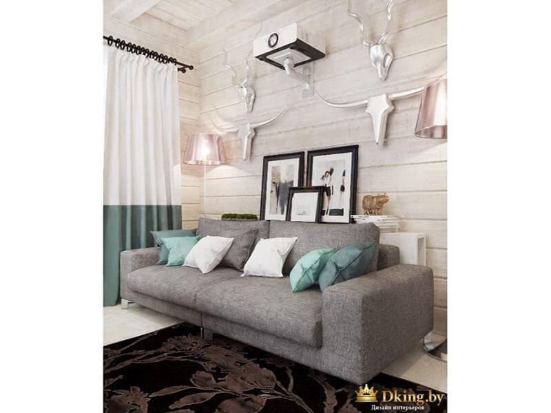 серый лаконичный диван с белыми и бирюзовыми подушками. белый пол и темно-коричневый ковер