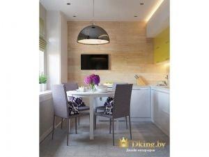 одна из стен на кухне выложена бежевой плиткой с природной текстурой. стол белый круглый, стулья современные серо-бежевые. шкафычики нижне белые с хромированными ручками - верхние - оливкового цвета. на потолке встроены споты и светодиодная подсветка над