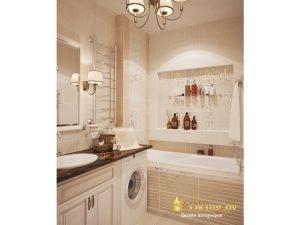 светлая бежевая ванная с классической люстрой и бра возле зеркала. Стиральная машина встроена под столешницу с умывальником. экран ванны из плитки