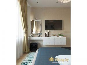 необычный подвесной туалетный столик белого цвета в спальне. над столиком зеркало, над подвесными полками - телевизор. вместо кресла использован мягкий пуф