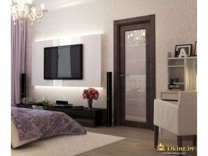 Интерьер спальни: кресло, дверь со стеклянной вставкой, плазменный телевизор на стене перед кроватью