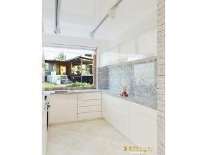 мозаичный серый фартук в сочетании с белой глянцевой кухней без ручек. Мойка перенесена под окно