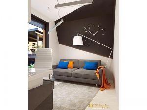 кабинет на втором этаже: шоколадная акцентная стена с часами, торшер, серый диван, светлый пол и основные стены