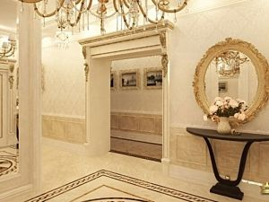 прихожая в стиле ампир: резной портал, круглое зеркало в багете, на полу панно из мраморной плитки