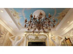 огромная люстра, состоящая более чем из 20 свечей, в месте крепления люстры расположена гипсовая белая розетка, потолок расписан в лучших дворцовых традициях: голубой фон сочетается с белыми, бежевыми и золотыми узорами