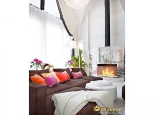шоколадный диван с яркими подушками на фоне белых стен и текстиля. в углу камин