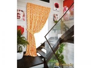 оранжевая штора с узором как декор окна в деревянном доме с белыми крашеными стенами. Деревянная лестница на второй этаж цвета венге. стелкянная перегородка в качестве перил