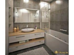 стена за зеркалом выложена серой плиткой. зеркало прямоугольное широкое. под умывальником выдвижные белые ящки, белая ванна, вместо шторки - стекляная панель. пол серый