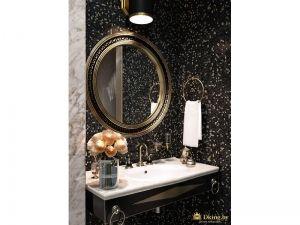 стена под зеркалом оформлена черной плиткойс рисунком мраморной крошки, зеркало круглое, рама и смесители бронзовые в ретро-стиле