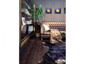 шикарный диван с обивкой бронзового цвета, на полу - ковер в виде шкуры. темные стены и пол в стиле ар-деко